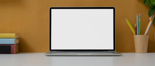 Creatieve werktafel met leeg scherm laptop, briefpapier en boeken op witte tafel met gele muur