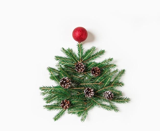 Creatieve winterlay-out gemaakt met groenblijvende boomtakken, dennenappels en rode kerstbal