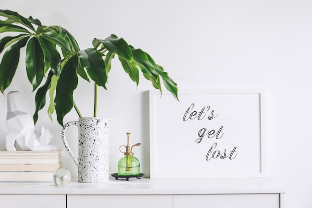 Creatieve woonkamer interieur met mock up poster frame witte moderne commode groen blad in creatief ontworpen vaas boeken en beeldhouwkunst van kat witte muren sjabloon