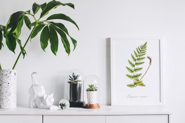 Creatieve woonkamer interieur met mock up poster frame witte moderne commode groen blad in creatief ontworpen vaasplanten in hipster ontworpen potten en sculptuur van kat witte muren sjabloon