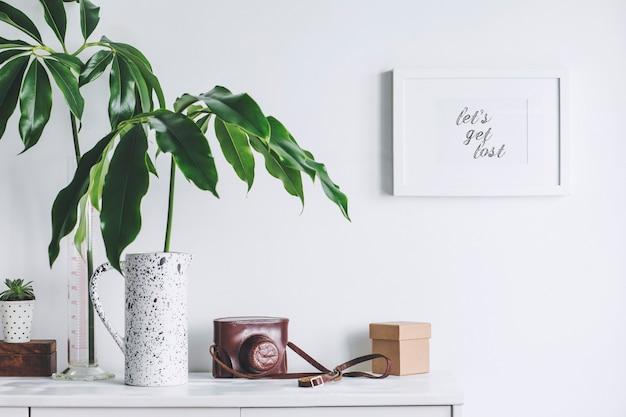 Creatieve woonkamer interieur met mock up poster frame witte moderne commode groene bladeren in creatief ontworpen vazen dozen en vintage cameratas witte muren sjabloon