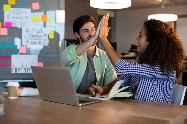 Creatieve zakenmensen geven elkaar high five aan balie op kantoor