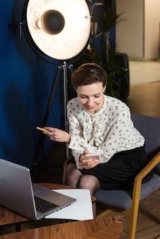 Creatieve zakenvrouw die op laptop in mooi donker kantoor werkt
