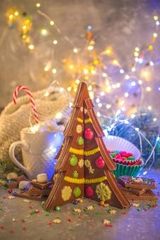 Creatieve zelfgemaakte chocolade in de vorm van een kerstboom met decoratie