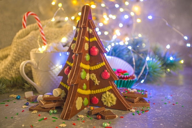 Creatieve zelfgemaakte chocolade in de vorm van een kerstboom met versieringen