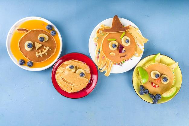 Creatieve zelfgemaakte halloween-pannenkoeken voor het ontbijt, in de vorm van grappige monsters, geest, vleermuis, heks. met traditionele trick or treat-snoepjes, snoep en decoraties, bovenaanzicht op kleurrijke blauwe achtergrond