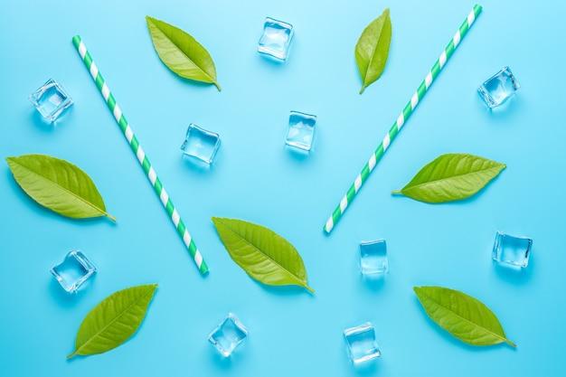 Creatieve zomersamenstelling met stro en ijsblokjes op blauwe ondergrond.
