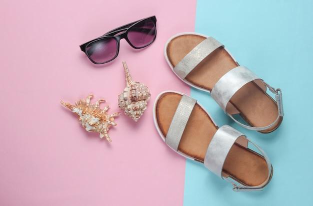 Creatieve zomerstrand plat leggen. leren damessandalen, schelpen, zonnebril op blauw-roze.