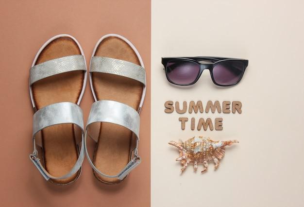 Creatieve zomerstrand plat leggen. leren damessandalen, schelpen, zonnebril op bruin met woorden zomertijd.