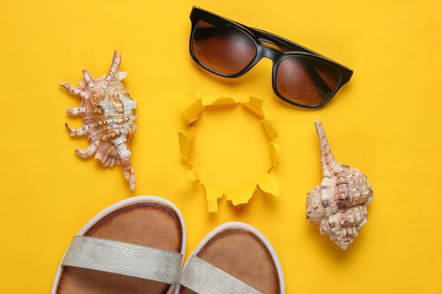 Creatieve zomerstrand plat leggen. leren damessandalen, schelpen, zonnebril op geel met gescheurd gat.