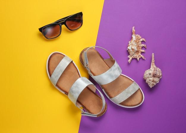 Creatieve zomerstrand plat leggen. leren damessandalen, schelpen, zonnebril op paars geel.