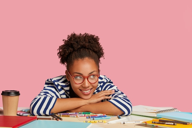 Creativiteit en inspiratie concept. tevreden glimlachende afro-amerikaanse grafisch ontwerper leunt aan tafel, heeft koffiepauze na tekening van foto in notitieboekje, geïsoleerd over roze muur in kunst
