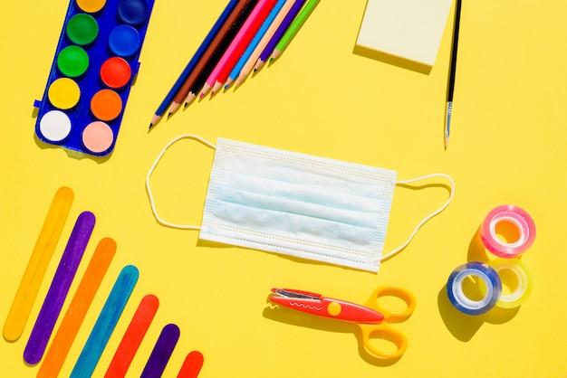 Creativiteit op school is ontwikkeld met kleurrijke materialen en met de bescherming van een masker om besmetting te voorkomen, platliggende achtergrond.