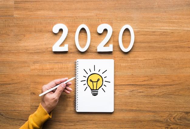Creativiteit van 2020 met gloeilamp tekenen op briefpapier.