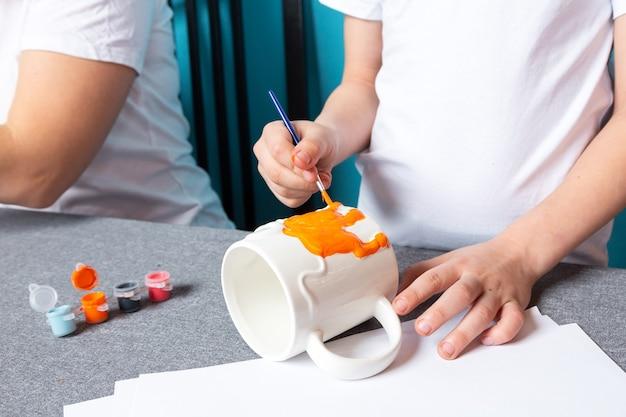 Creativiteit van kinderen. close-up van de jongen verf met verf op blauwe achtergrond, bovenaanzicht