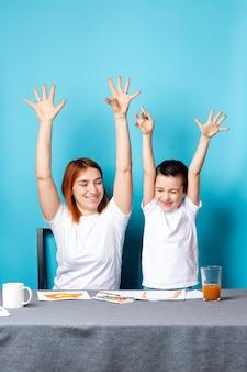 Creativiteit van kinderen. moeder en kind zoon schilderen aquarel huiswerk voor de kleuterschool en steken vreugdevol hun handen omhoog op blauwe achtergrond