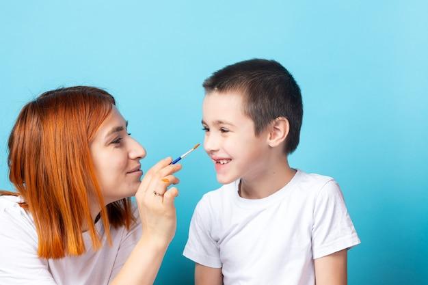 Creativiteit van kinderen. moeder en zoon dollen rond en schildert zijn neus met een penseel op een blauwe achtergrond