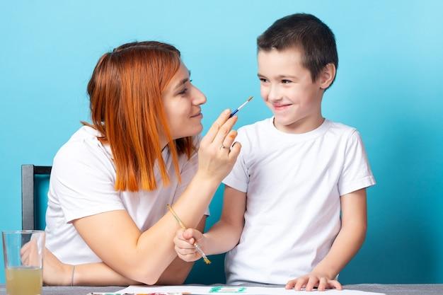 Creativiteit van kinderen. moeder en zoon schilderen en hebben plezier, moeder schildert een neus voor haar zoon met een penseel op blauwe achtergrond