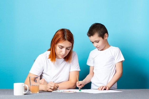 Creativiteit van kinderen. moeder en zoon schilderen met verf op blauwe achtergrond
