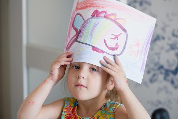 Creativiteit van kinderen. weinig kindmeisje trekt thuis met waspotloden. het concept van afstandsonderwijs online voor de periode van wereldwijde quarantaine.