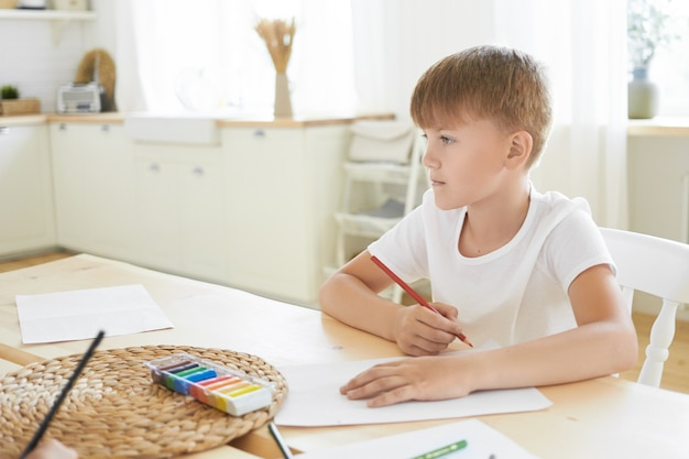 Creativiteit, vrije tijd, hobby, kunst en verbeelding concept. foto van doordachte blanke schooljongen in wit t-shirt zit aan bureau binnenshuis, nadenkend kijken, denken wat te tekenen met potlood