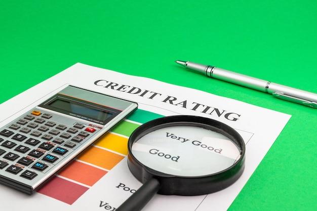 Credit rating met pen, rekenmachine en vergrootglas op een groene tafel.