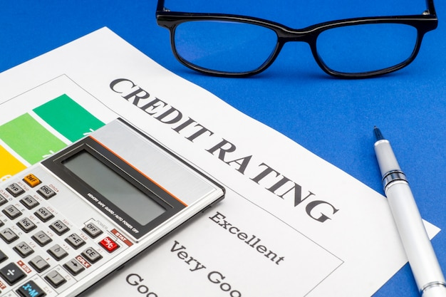 Credit rating op een blauwe tafel, pen, glazen.