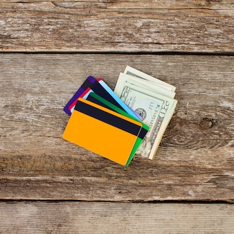 Creditcard en dollars op houten achtergrond.