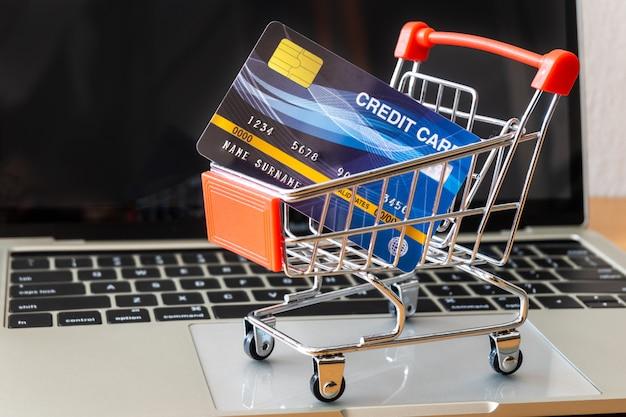 Creditcard en kar supermarkt op houten tafel. winkelen concept