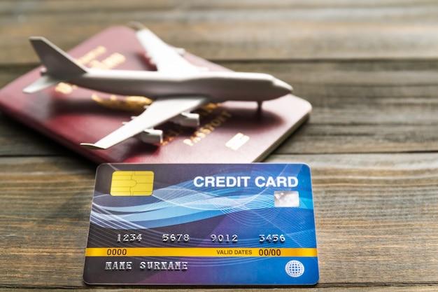 Creditcard op houten bureau gezet met paspoort en plan, voorbereiding voor reizen concept