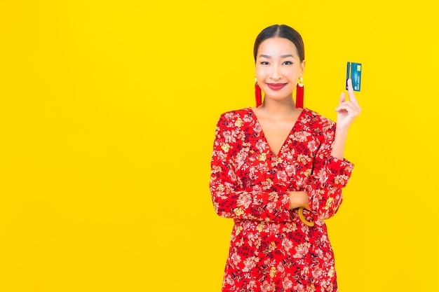 Creditcard van de portret de mooie jonge aziatische vrouw om op gele geïsoleerde muur te winkelen