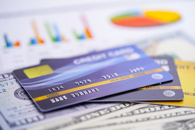 Creditcardmodel op amerikaanse dollarbankbiljetten met grafiek en grafiekspreadsheetpapier.