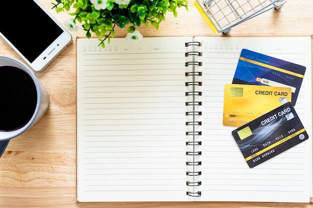 Creditcards, notebook, bloempot boom, smartphone, winkelwagen en koffiekopje op houten achtergrond, online bankieren bovenaanzicht office tafel.