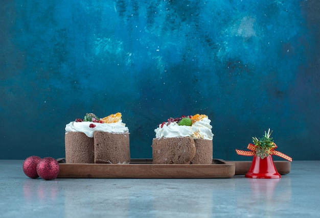 Crème bedekte taarten en kerstballen op marmer.