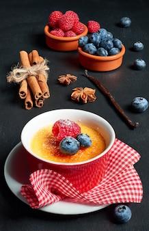 Crème brulee (crème brulee, verbrande room) met framboos en bosbes
