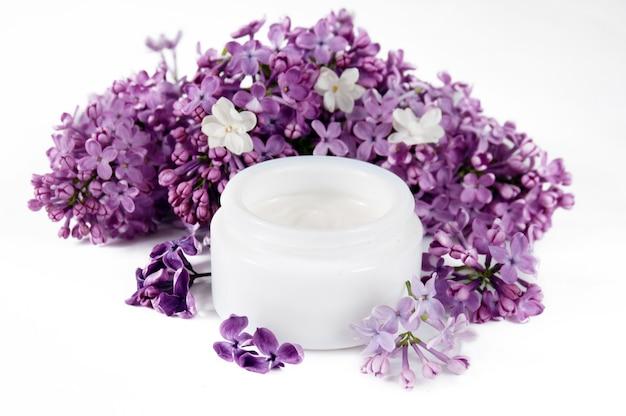Crème cosmetica en extract in lila cosmetica met bloemen op witte achtergrond
