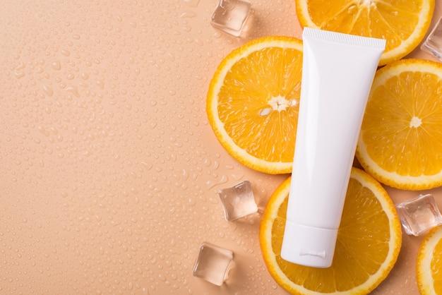 Crème fles liggend op plakjes oranje fruit