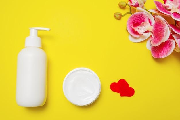 Crème in een fles en pot, harten en orchideeën op een gele achtergrond, een compositie voor moederdag.