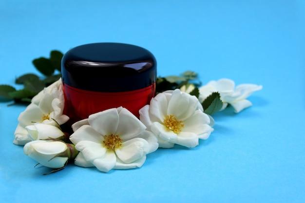 Crème in het rood in een fles omgeven door witte rozenbottels op een blauwe achtergrond voedende cosmetica voor het gezicht