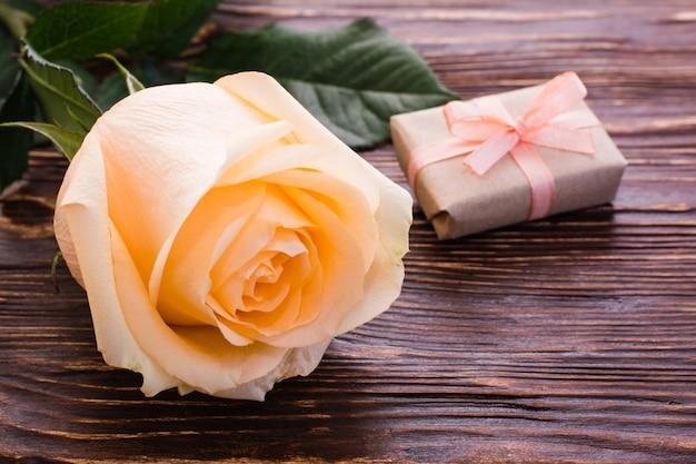 Crème roos en een geschenk op houten tafel