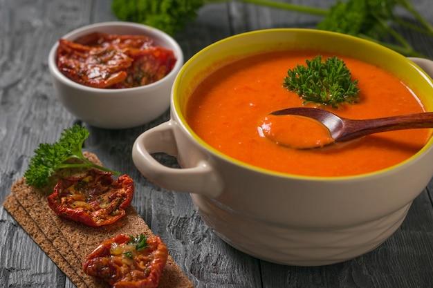 Crème van paprika soep met selderij met gedroogde tomaten op een houten tafel. soep van het vegetarische dieet.