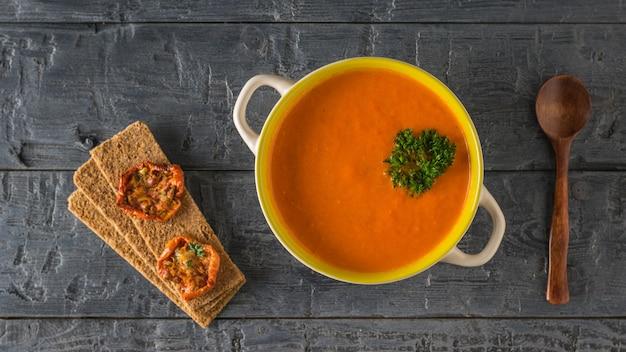 Crème van pepersoep met een houten lepel en broodtoost. soep van het vegetarische dieet. plat leggen. het uitzicht vanaf de top.