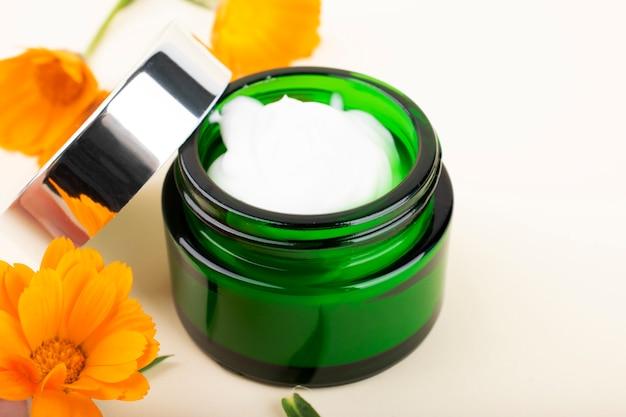 Crème voor gezicht en lichaam. groene pot met calendula crème en oranje bloemen.