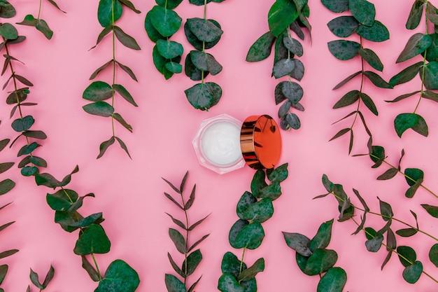 Crème voor huidverzorging op de bank ligt op de roze tafel, rond de bladeren en takken van eucalyptus