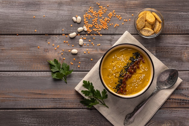 Crèmesoep met bonen en kruiden op een servet op een houten tafel in de buurt van een kom met crackers en bonen