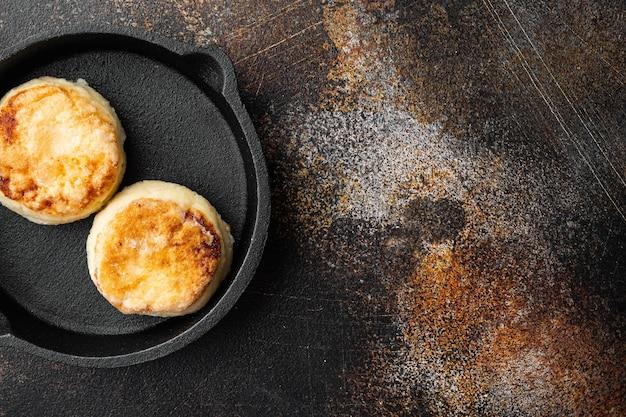 Crêpe beignets van kwark op gietijzeren koekenpan op gietijzeren koekenpan, bovenaanzicht plat lag, op oude donkere rustieke tafel
