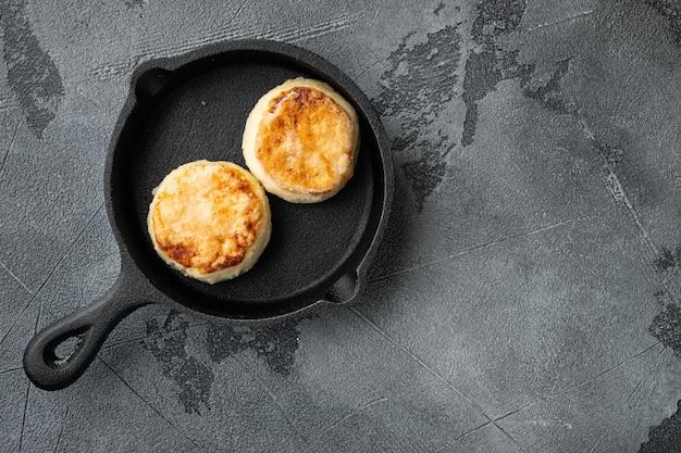 Crêpe beignets van kwark op gietijzeren koekenpan op gietijzeren koekenpan, bovenaanzicht plat, op grijze stenen tafel