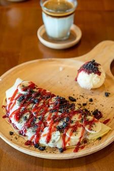 Crêpe met banaan, slagroom en aardbeiensaus op houten plaat