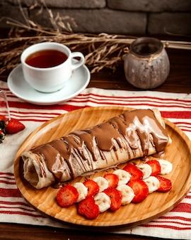 Crepe met vruchten aardbei banaan chocolade thee zijaanzicht