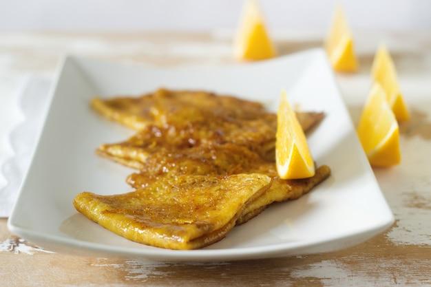 Crêpe suzette in karamelsaus op een bord met een schijfje sinaasappel. frans dessert.